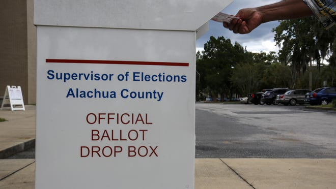 A person drops off their early voting ballot at the Alachua County Supervisor of Elections Office in Gainesville on Aug. 8.