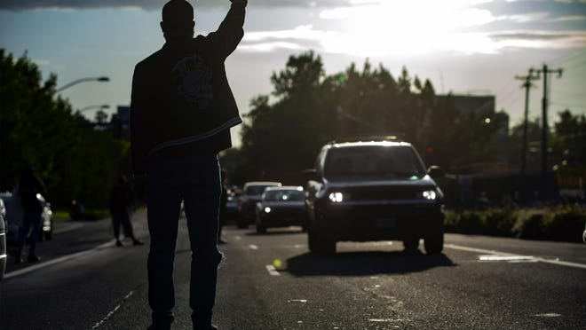 Isiah Wagoner holds his fist in the air as traffic flows by on Franklin Boulevard after protesters arrived at Matthew Knight Arena in June 6 and the road was cleared. [Andy Nelson/The Register-Guard file] - registerguard.com