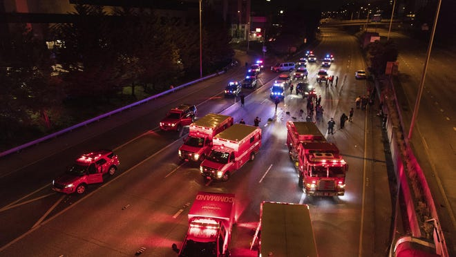 Emergency personnel work at the site where a driver sped through a protest-related closure on the Interstate 5 freeway in Seattle. Dawit Kelete, 27, has been arrested and booked on two counts of vehicular assault.