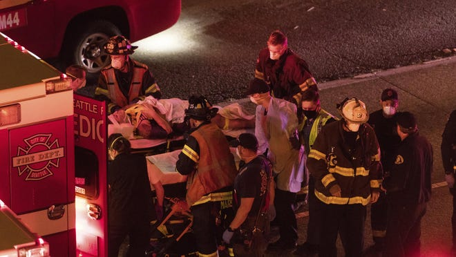 Emergency workers bring an injured person to an ambulance after a driver sped through a protest-related closure on the Interstate 5 freeway in Seattle, authorities said early Saturday, July 4, 2020. Dawit Kelete, 27, has been arrested and booked on two counts of vehicular assault.