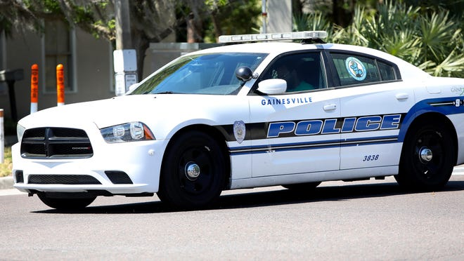 A officer with the Gainesville Police Department drives south on NW Sixth Street near the GPD station in Gainesville on March 19.