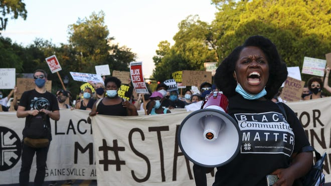 Desmon Duncan-Walker leads cheers during a march against turning the Seminary Lane property in the Pleasant Street Historic District in Gainesville into a student housing complex Thursday evening.