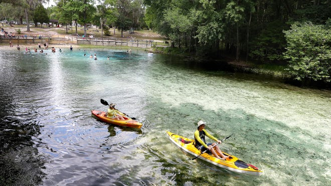 A group of canoers paddle away from the spring head at Gilchrist Blue Springs State Park north of High Springs on May 20.