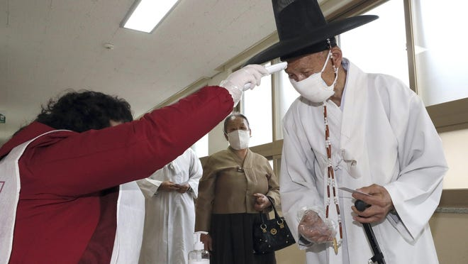 A South Korean Confucian scholar wearing a face mask to help protect against the spread of the new coronavirus has his temperature checked upon his arrival to cast his vote for the parliamentary elections at a polling station in Nonsan, South Korea, Wednesday, April 15, 2020. South Korean voters wore masks and moved slowly between lines of tape at polling stations on Wednesday to elect lawmakers in the shadows of the spreading coronavirus.