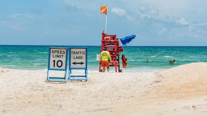 A lifeguard pushes his tower over across the soft sand.