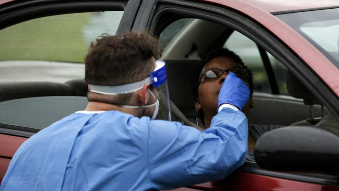 Victor Silva, a UF medical student, conducts a COVID-19 test on Chinyere Afi-Leigh at Citizen's Park in northeast Gainesville on Saturday. The city offered free drive-thru testing on a first-come, first-served basis.