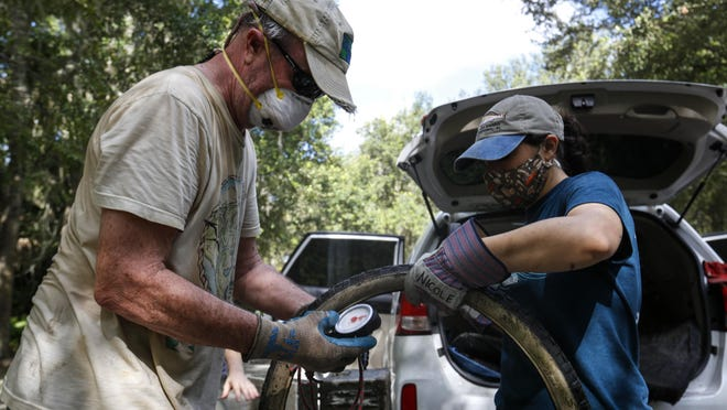 Dan Rountree and Nicole Llinas from the environmental nonprofit organization Current Problems weigh a tire they pulled from the creek at Sweetwater Park in Gainesville on Saturday. The organization hosts cleanup days and measures the amount of litter they pick up by weight.