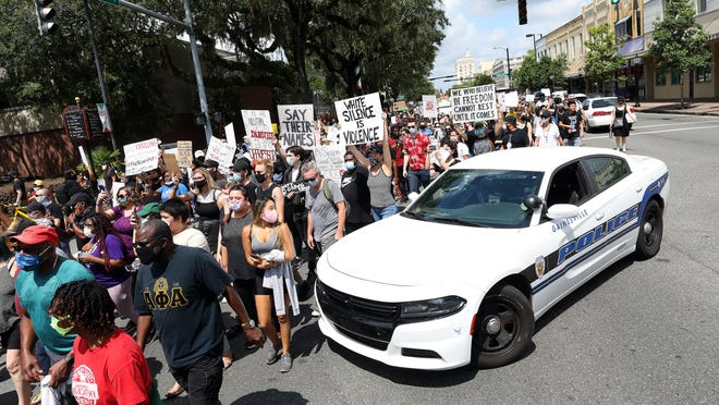 Protesters make their way past a Gainesville Police Department car blocking traffic on University Avenue as they take part in a May 30 march in response to the killing of George Floyd by a police officer in Minneapolis.