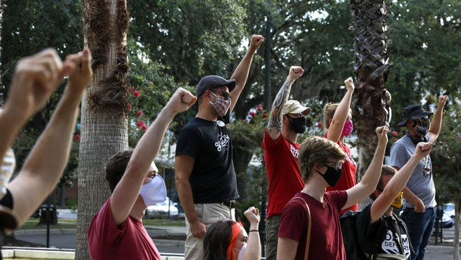 Activists raise their fists in support as Wallace Mazon speaks on Sunday in front of Gainesville City Hall during a rally to support defunding the Gainesville Police Department. The event was organized by Gainesville Socialist Alternative with Dream Defenders.
