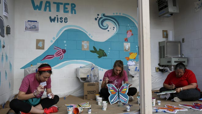 Alaina Carpenter, Anna Massey and Ana Irimia paint butterflies for the outdoor classrooms at C.W. Norton Elementary School in Gainesville back on Feb. 23. The School Board has pushed back the start date for the 2020-21 school year.