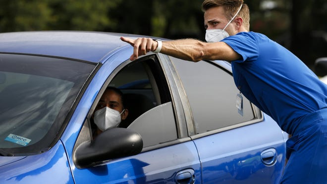 Joe Calpin, a second year University of Florida medical student and leader of a COVID-19 testing project, helps direct vehicles to test sites at Citizen's Field in Gainesville on June 27.