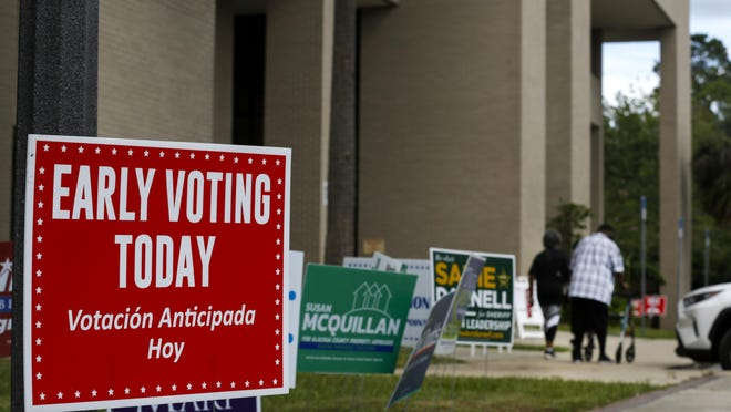 People walk to their car after voting early at the Alachua County Supervisor of Elections Office in Gainesville on Saturday.