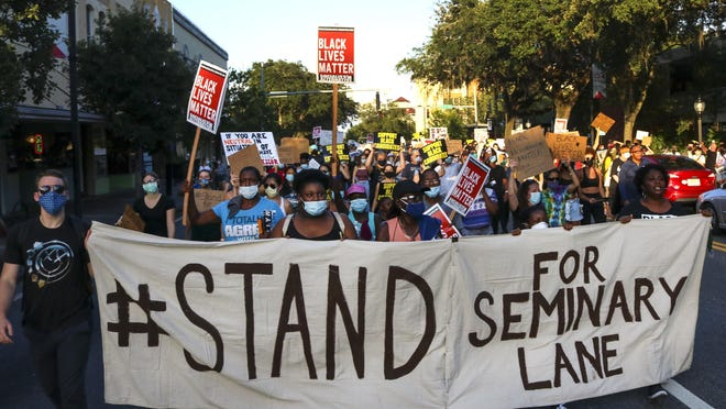 More than 300 protestors march through Gainesville against a proposal to turn the Seminary Lane property in the historic Northwest Fifth Avenue neighborhood into a student housing complex on June 18.