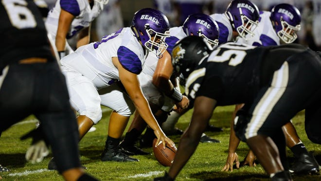 Fletcher (left) and Buchholz linemen face off across the line of scrimmage at a 2019 high school football game.