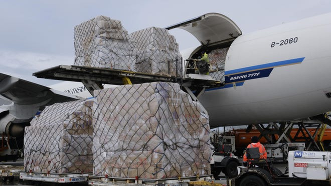 A ground crew at Los Angeles International Airport unload pallets of medical personal protective equipment from a China Southern Cargo plane upon its arrival in Los Angeles in April. California will spend $315 million more to buy hundreds of millions of protective masks as the coronavirus continues to ravage the state.