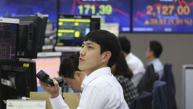 A currency trader watches monitors at the foreign exchange dealing room of the KEB Hana Bank headquarters in Seoul, South Korea, Wednesday, June 3, 2020. Asian shares are rising after Wall Street extended its gains for the third straight day, driven by optimism over economies reopening from shutdowns to stem the coronavirus pandemic.