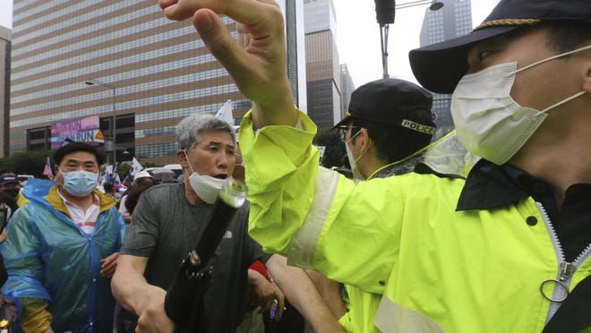 A protester argues with a police officer during a rally against the government in Seoul, South Korea, Saturday, Aug. 15, 2020. Thousands of anti-government protesters, armed with umbrellas and raincoats, marched through the soggy streets of South Korea's capital Saturday, ignoring official pleas to stay home amid a surge in coronavirus infections.