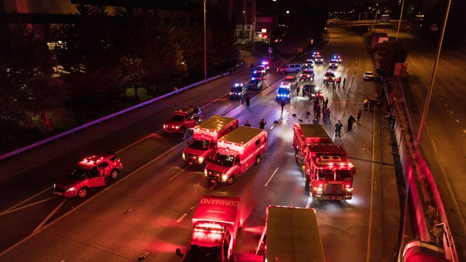 Emergency personnel work at the site where a driver sped through a protest-related closure on the Interstate 5 freeway in Seattle early Saturday and struck two protesters, killing one.