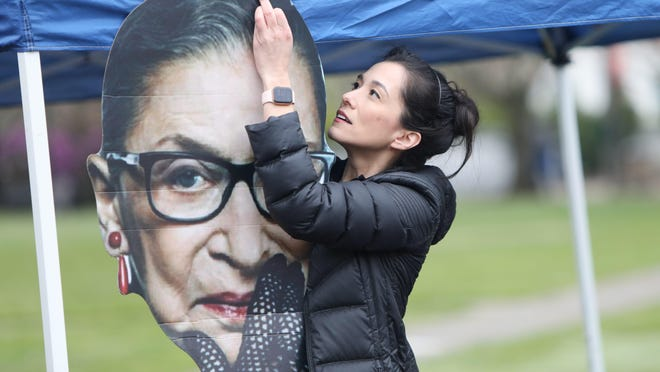 Christel Allen, political director at NARAL Pro-Choice Oregon, hangs a cut-out of U.S. Supreme Court Justice Ruth Bader Ginsburg's head on the NARAL booth during the Women's March at the Oregon State Capitol Mall in March.