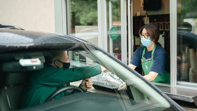 A Starbucks customer picks up his order at the store's drive-thru window.