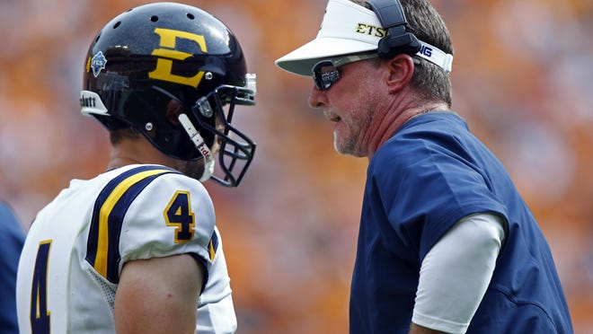 East Tennessee State University head coach Randy Sanders talks with quarterback Logan Marchi in the first half of an NCAA college football game against Tennessee Saturday, Sept. 8, 2018, in Knoxville, Tenn.