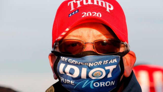A Donald Trump supporter wears an anti Gretchen Whitmer mask at a Trump rally in Grand Rapids, Michigan, on Nov. 2, 2020.