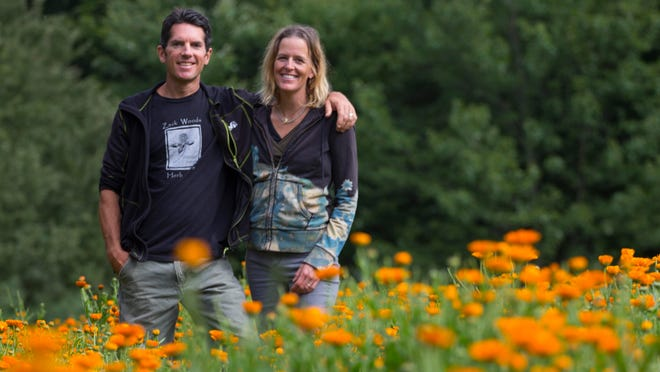 Melanie and Jeff Carpenter of Zack Woods Herb Farm stand surrounded by Calendula blooming in their fields in Hyde Park. The couple farm 10 acres of organic herbs and sell largely to wholesale accounts.