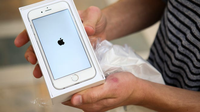 A customer who camped outside Oxmoor Center unveils his iPhone 6 after leaving the Apple store last week.