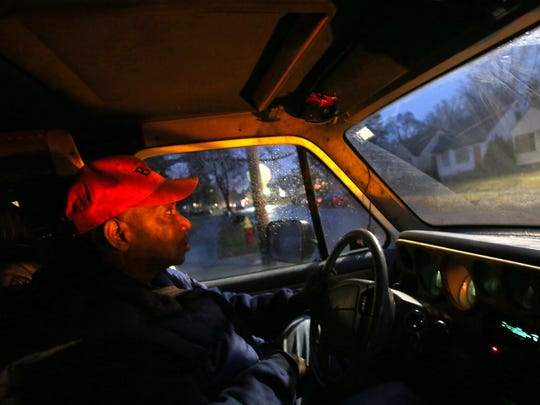 The flashing yellow light mounted on the hood of his van lights up the interior as Jimmie Lockhart, 61 of Detroit patrols the streets of Detroit.