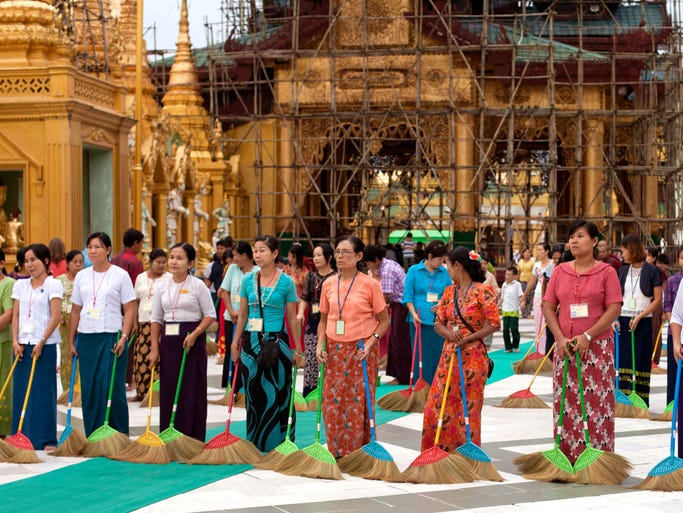 A group of Buddhist devotees stand to begin sweep on platform at Myanmar famous Shwedagon Pagoda in Yangon, Myanmar. Every evening, more than a dozen men and women walk in a tight row in front of Myanmar's most revered Buddhist pagoda, sweeping the vast marble terrace in unison in hopes of keeping it clean for barefoot pilgrims. To these volunteers, this is not a chore but a noble act, one they carry out eagerly in an effort to gain merit, or spiritual credit. (AP Photo/Khin Maung Win)