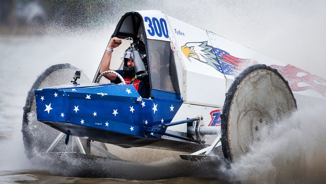 Tyler Johns throws his arms in the air as he crosses the finish line, winning the final race with his buggy, The Patriot, during the Swamp Buggy Races Winter Classic on Sunday at the Florida Sports Park in East Naples. It was a triumph on many levels for Johns, who was narrowly defeated 10 months ago in his comeback race after losing part of his left arm in an airboat accident in 2016. And last fall's racing was canceled because of damage from Hurricane Irma.