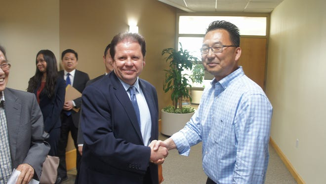 Mayor James Rotundo (left) shakes hands with Councilman Christopher Chung.