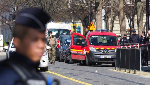 French police officers take position after letter bomb exploded at the French office of the International Monetary Fund, lightly injuring one person, Thursday, March 16, 2017. A police official said no other damage was been reported in the incident.