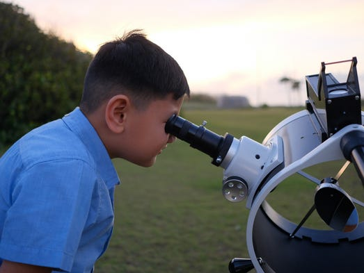 Ayden Lumanog gets his eye up close to the telescope