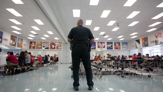 A school resource officer with the Lee County Sheriff's Office works in the cafeteria at North Fort Myers Academy of the Arts in 2013.