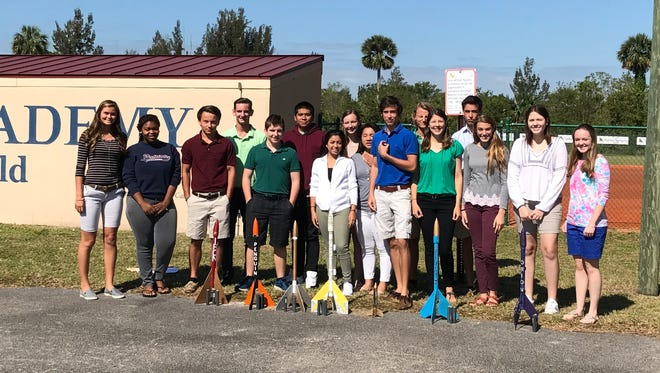 Master's Academy 10th-graders stand with their rocket projects.