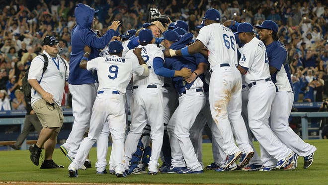 Dodgers players jump on starting pitcher Clayton Kershaw (22) after he pitched a no-hitter against the Colorado Rockies at Dodger Stadium on Wednesday.