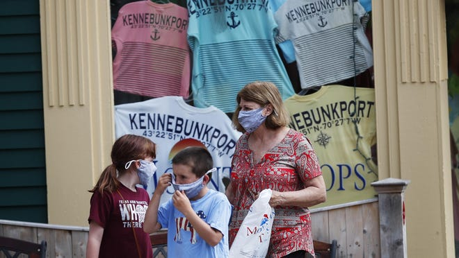 Visitors walk by a souvenir T-shirt shop Tuesday, June 23, 2020, in Kennebunkport, Maine. The coronavirus pandemic has hurt many of Maine's businesses that rely on just a few months in the summer for most of their annual revenue.