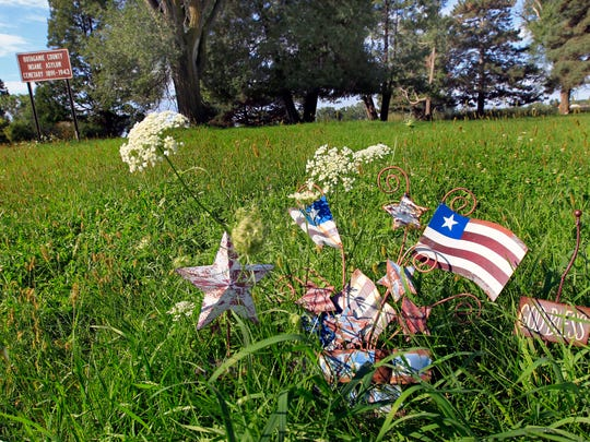 Memorials are left on the grounds of the Outagamie County Insane Asylum Cemetery earlier this month in Grand Chute.