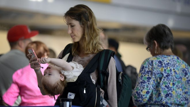 Ann Walden checks her phone as her daughter Delphine plays while waiting in line after their flight to Baton Rouge was delayed at O'Hare International Airport in Chicago.