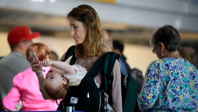 FILE - In this Friday, Sept. 26, 2014, file photo, Ann Walden checks her phone as 15-month-old daughter Delphine plays while waiting in line after their flight to Baton Rouge was delayed at O'Hare International Airport in Chicago. There are several ways to distract and soothe little ones when traveling by air.