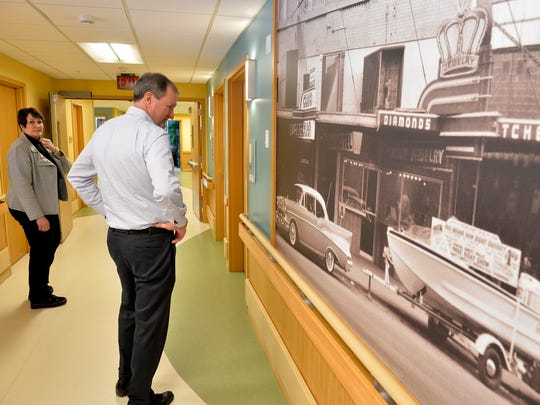 Benefis Health  System CEO John Goodnow views old photos on display in the memory care unit.