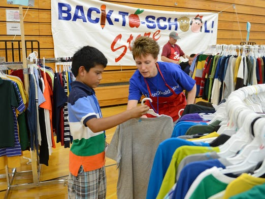 Volunteer Bonnie Tennie helps Andrew Garcia pick out clothing during the Service League's 22nd Annual Back to School Store, at Green Bay East High School, Wednesday, August 6, 2014.