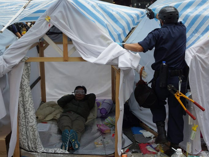 A pro-democracy protester rests in his tent as police