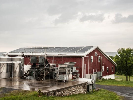Winemaking equipment is in the foreground and solar