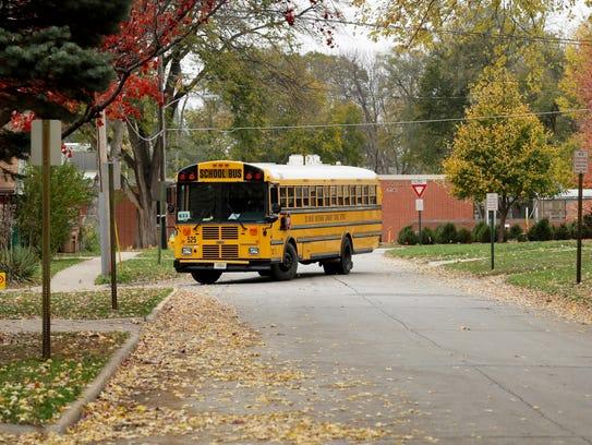 A school bus makes a turn down a street with no sidewalks,