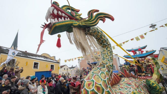 Revelers on a dragon float participate in the traditional 'Chinese carnival procession' in Dietfurt, Germany, on Feb. 12, 2015. The 'Chinese carnival' is based on a legend according to which the citizens of Dietfurt let a tax collector stand outside the town wall in the Middle Ages. According to the legend, the treasurer complained to the bishop, his lord, that the citizens of Dietfurt would hide behind their wall like the Chinese.