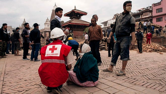 Rescue workers from the Nepal Red Cross Society help injured people  April 25, 2015, in Katmandu, Nepal. New tremors sent shocked survivors scurrying outdoors just 24 hours after a devastating magnitude-7.8 earthquake shook the region that has taken the lives of at least 2,500 people.