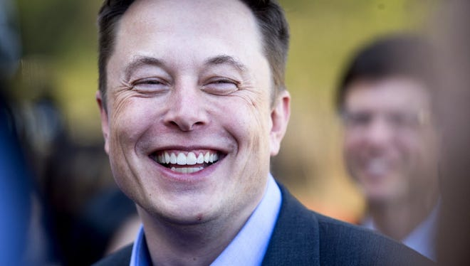 n this April 30, 2015, file photo, Tesla CEO Elon Musk speaks with members of the media at Tesla's headquarters in Palo Alto, Calif.