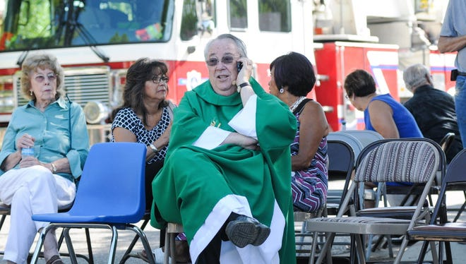 While waiting in a staging area, Holy Cross Catholic Church Pastor John Anderson tries to get in touch with other local churches to warn them after two explosions occurred on Sunday, Aug. 2, 2015, in Las Cruces, N.M. Churchgoers were left shaken during Sunday morning services after authorities say the explosions occurred less than 30 minutes apart.